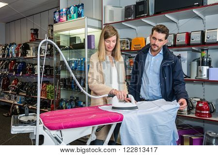 Young couple testing iron by ironing shirt in home appliance hypermarket