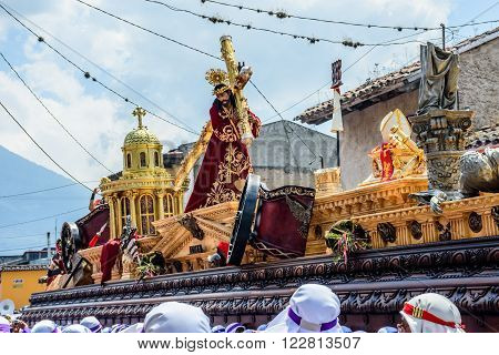 Antigua Guatemala - March 20 2016: Float bearers carry float with Jesus in Palm Sunday procession in colonial town with most famous Holy Week celebrations in Latin America. Slope of Agua volcano behind.