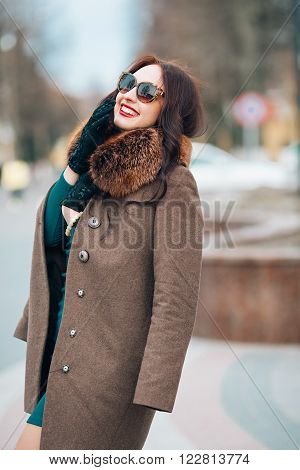 Young beautiful sexy brunette girl, woman with chic long dark hair in stylish sunglasses, elegant fur coat with fur and gloves smiling posing on the street trendy makeup