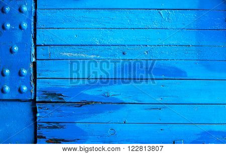 Brightly painted blue wooden background texture with weathered boards and a corner metal plate with studs