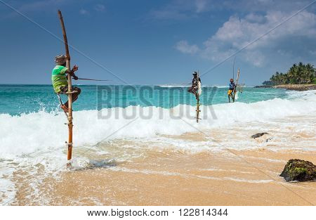 Galle, SRI LANKA- FEB 9: The local fishermen are fishing in unique style on February 9, 2013 in Galle, Sri Lanka.