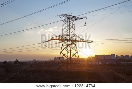 Electricity pylon against the sunset and the high-rise Kyiv (Ukraine) buildings in the distance.