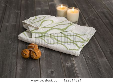 Towels With Green Concave Lines Alongside Candles And Dried Citrus