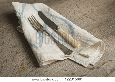 Fork And Knife On White Napkin With Blue Concave Lines