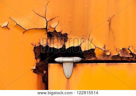 Old cracked and corroded rusty hinge detail of orange metal door with copy space