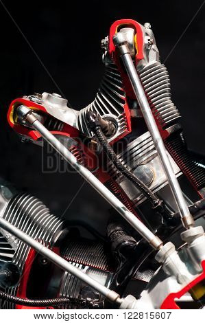 Close up on engine with spark plugs as part of museum display under soft lighting with black background