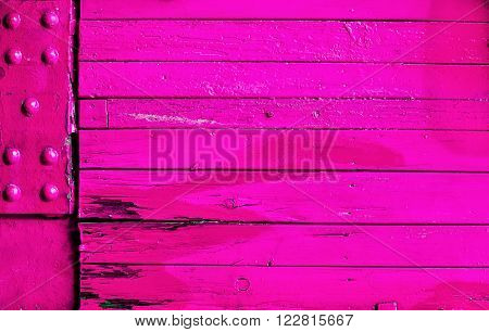 Vibrant pink wood and metal background texture with old stained weathered wooden boards and a metal corner plate with studs