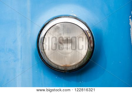 Front round chrome headlight of a vintage car with a single lens and blue bodywork close up view