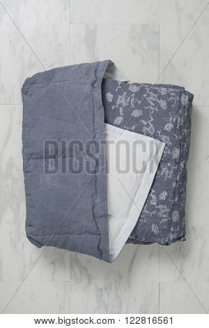 Folded Dark Gray Duvet With Floral Accents And Underside Exposed
