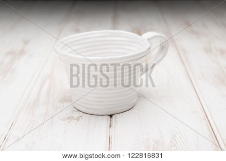 White Teacup On A White Wooden Panel Surface