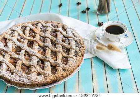 Baked homemade rustic style tart pie with apple jam in ceramic dish next to a cup of coffee, white napkin and cinnamon sticks in a glass jar,star anice on the background over wooden turquoise table close-up, selective focus