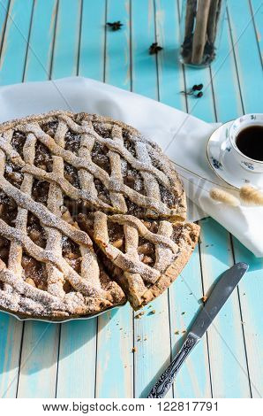 Baked homemade rustic apple tart pie with cutted piece in ceramic dish next to a cup of coffee white napkin knife with cinnamon in glass jar on the background over wooden turquoise table natural side sunlight selective focus