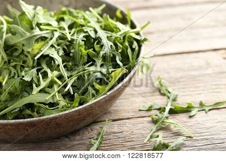 Fresh arugula leafs on a grey wooden table