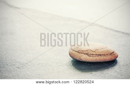Retro toned stone on a slate, natural background with copy space, shallow depth of field.