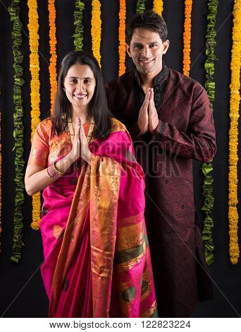 Portrait of Maharashtrian couple holding both hands together in prayer position, indian couple doing or performing pooja, indian couple celebrating diwali, laxmi pujan, asian couple doing prayer
