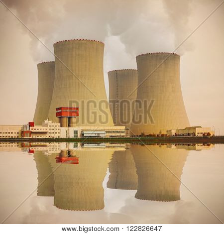 Nuclear power plant on the coast. Industrial and ecology disaster concept. Warm filtered picture.