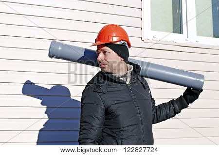 Worker at a construction site in an orange helmet with a sewer pipe in his hand