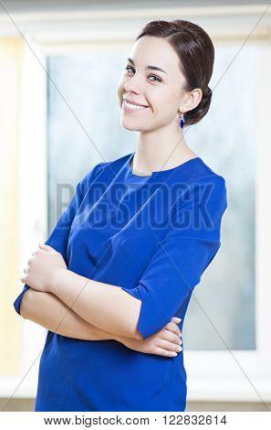 Portrait of Smiling Caucasian Brunette Woman In Stylish Blue Dress Posing Indoors.Vertical Shot