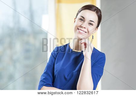 Portrait of Positive Smiling Caucasian Brunette Woman In Stylish Blue Dress Posing Indoors.Horizontal Shot