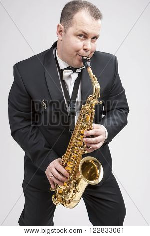 Portrait of Expressive Caucasian Player in Suit Playing on Saxophone.Vertical Composition