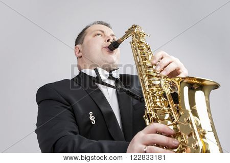 Music Themes and Ideas. One Caucasian Male Saxophonist Playing Saxophone in Studio. Against White. Horizontal Image