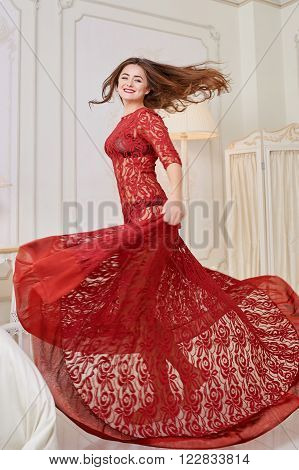 Happy woman in a red dress jumping out of bed.