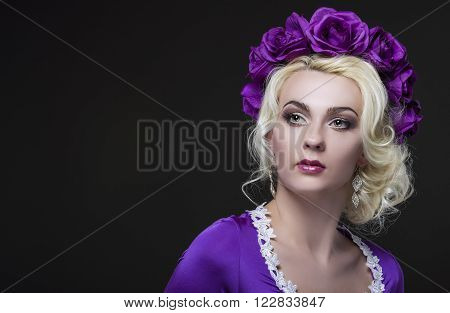 Fashion and Beauty Concepts. Portrait of Blond Caucasian Female With Purple Flowery Crown Against Black.Horizontal Image