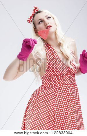 Pinup Retro Concepts. Dreaming Sensual Pinup Blond Woman With Sweet Candy Posing in Polka Dotted Dress on White. Vertical Image Orientation