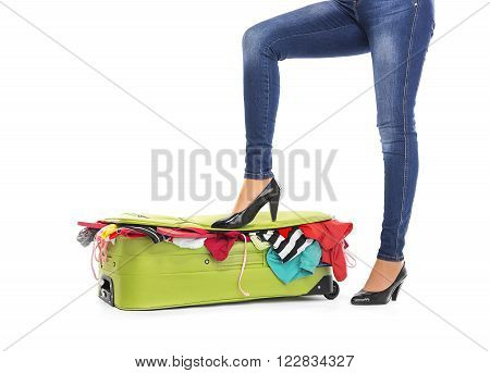 Female feet in shoes on a suitcase. White background.