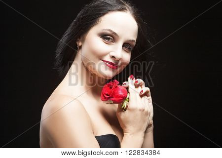 Portrait of Caucasian Brunette Female Posing With Rose Against Black Background. Horizontal  Image Orientation