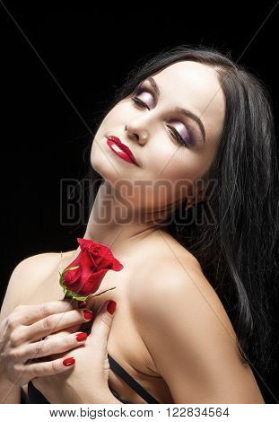 Portrait of Sensual Vulnerable Caucasian Brunette Woman Posing With Rose Flower Against Black Background. Vertical Shot