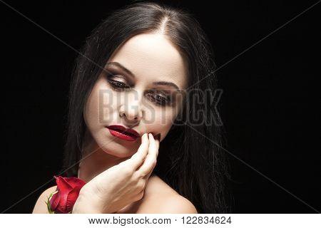 Portrait of Sensual Vulnerable Caucasian Brunette Woman Posing With Rose Flower Against Black Background. Horizontal Shot