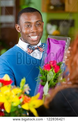 Handsome man purchasing roses at a florist shop