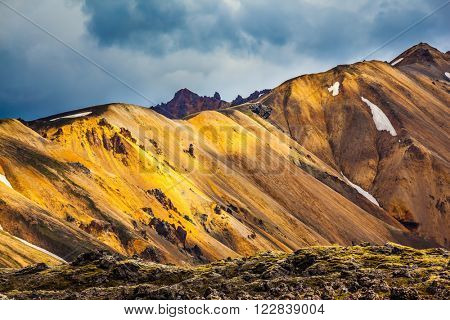 Multicolored rhyolite mountains scenic highlights the July sun. Travel to Iceland in the summer