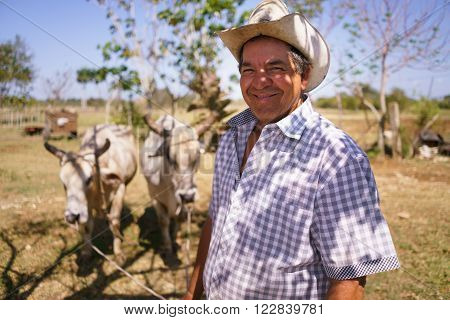 Farming and cultivations in Latin America. Portrait of middle aged hispanic farmer sitting proud in his tractor at sunset holding the volante. He looks at the camera and smiles happy.