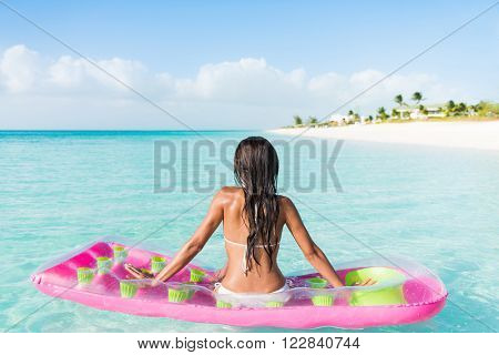 Beach relaxation woman floating on pink inflatable air bed pool mattress toy float in ocean beach background in pristine blue turquoise water at luxury caribbean getaway resort.