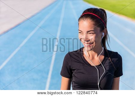 Happy track running girl runner listening to music motivation with earphones getting ready for cardio training run on blue lane athletic tracks in stadium campus. Healthy Asian athlete.