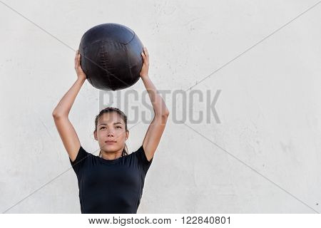 Fitness crossfit girl holding medicine ball above head for shoulder press workout in outdoor crossfit gym. Young Asian athlete girl doing upper body exercise working out with heavy weighted balls.