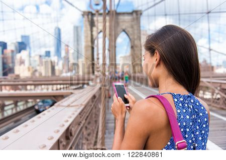 Smartphone texting girl on Brooklyn bridge in urban New York City, Manhattan USA. View from the back of unrecognizable business woman holding phone reading or using social media in summer.
