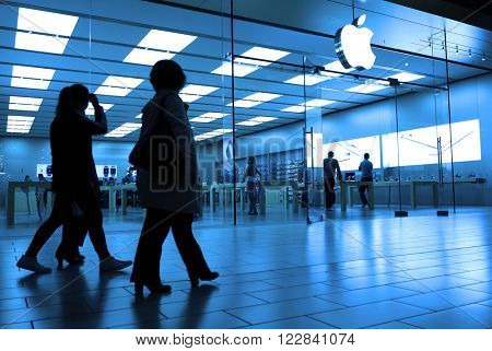Coquitlam, BC, Canada - October 09, 2015 : One side of people shopping inside Apple store with blue toned