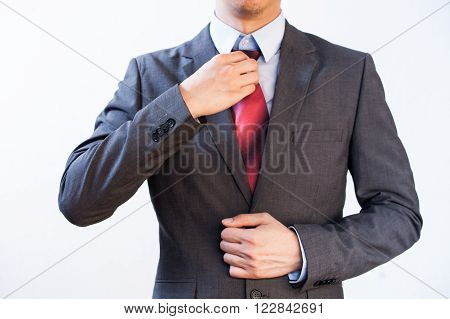 Businessman Executive adjusting red tie isolated on white background