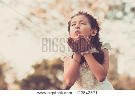 Lovely little girl blowing a kiss to somebody