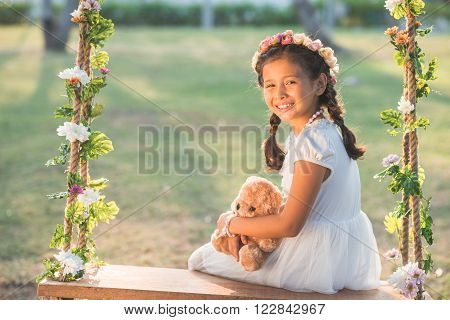 Preteen smiling girl sitting on decorated swing in the park