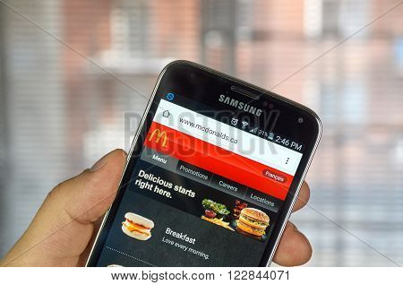 MONTREAL CANADA - MARCH 20 2016 - McDonald's site on Samsung S5's screen. McDonald's is the world's largest chain of hamburger fast food restaurants.