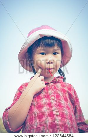 Cute Little Asian Girl Eating A Lollipop On Nature Background In Summertime. Cross Process. Vintage