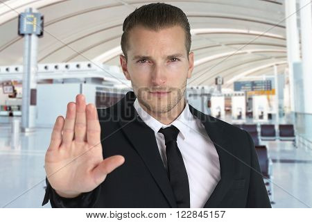 security officer raising his hand in front of  an airport