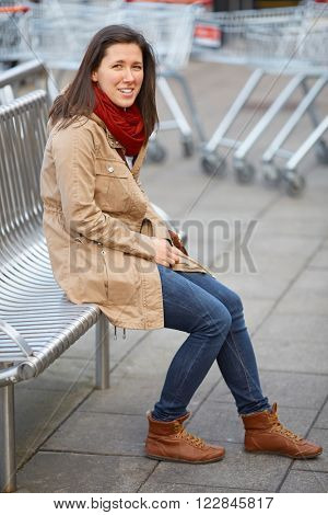 Young female siting on metal bench with shopping troleys at background