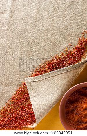 Dried saffron spice on a linen napkin and ground saffron