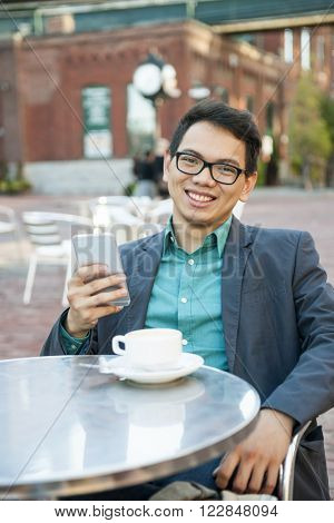 Successful young asian man in business casual attire sitting and smiling in relaxing outdoor cafe with cup of coffee and mobile device