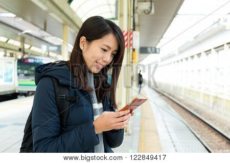 Woman usinf mobile phone at train platform